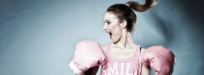 Female boxer model with big fun pink gloves playing sports boxing hair motion blue background